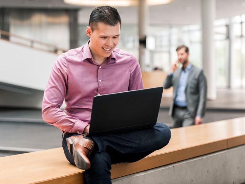 Ein Mann sitzt auf einer Bank und schaut auf seinen Laptop