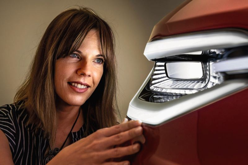 Woman looking at a front light of a car