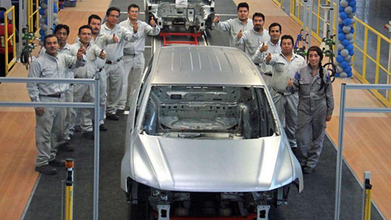 Historia de Volkswagen México - Empleados dentro de planta VW rodeando automóvil en producción