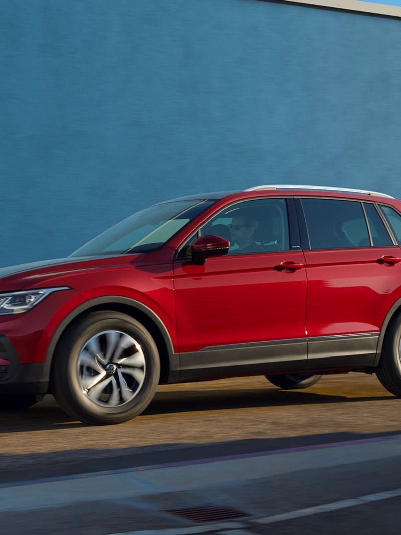 Roter VW Tiguan ACTIVE fährt in urbaner Umgebung vor einer blauen Fassade.