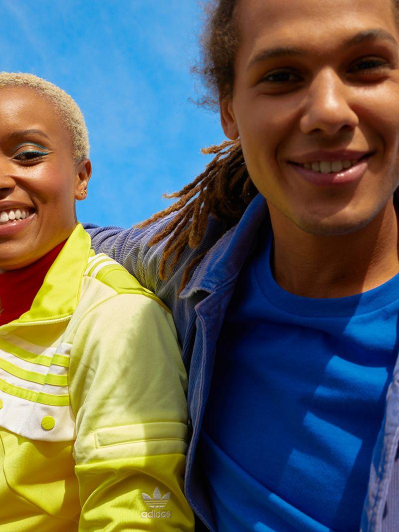 Ein fröhliches Paar mit gelbem und blauem Hemden vor blauem Himmel. Lifestyle.