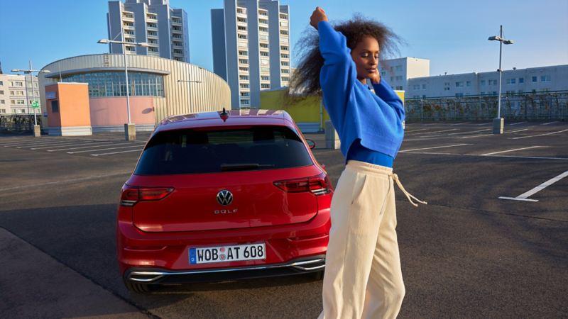 Heckansicht des roten VW Golf ACTIVE. Davor eine Frau.