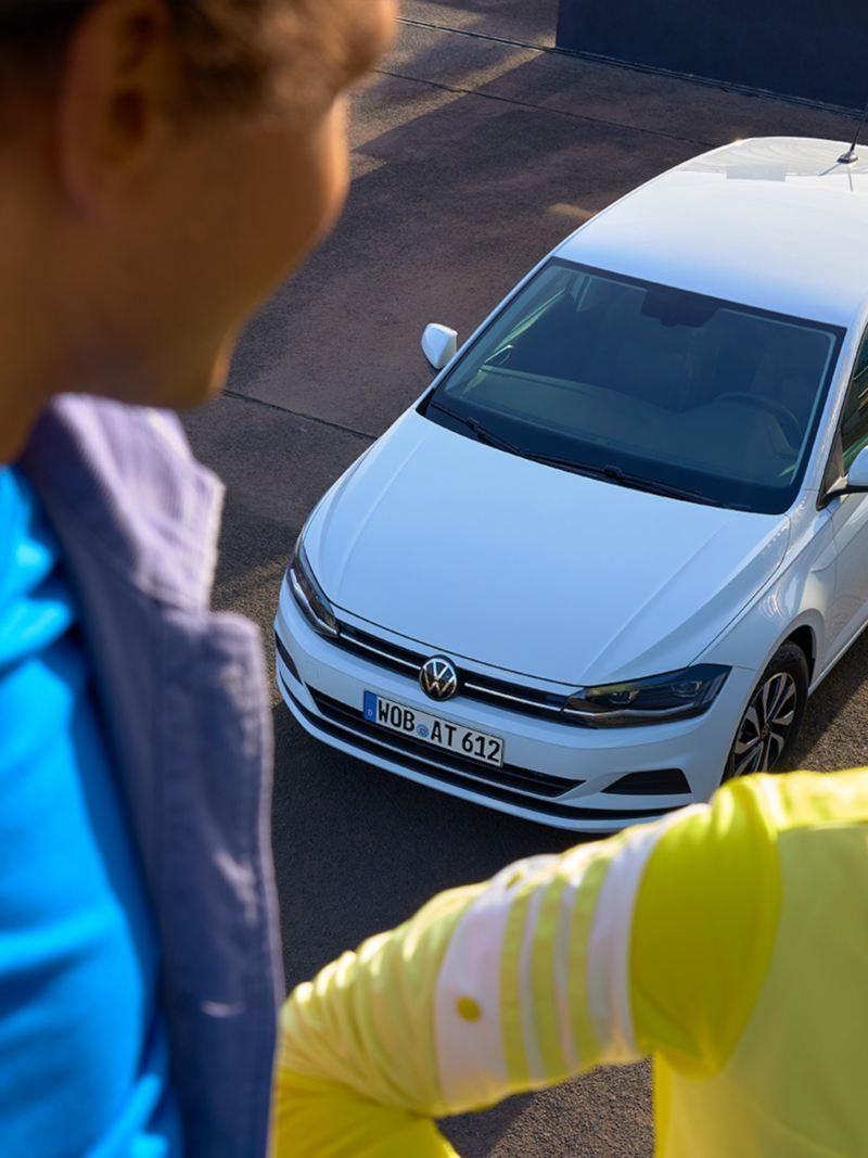 Blick von oben auf den weißen VW Polo ACTIVE. Im Vordergrund sind ein Mann und eine Frau zu sehen.