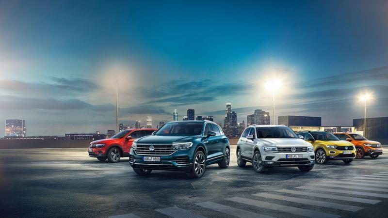 VW SUVs Tiguan, Touareg, Tiguan Allspace, T-Roc und T-Cross vor einer Stadt