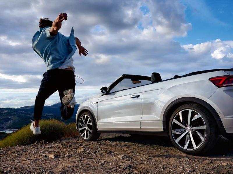 Un uomo salta di gioia vicino alla sua Volkswagen cabrio parcheggiata in montagna.
