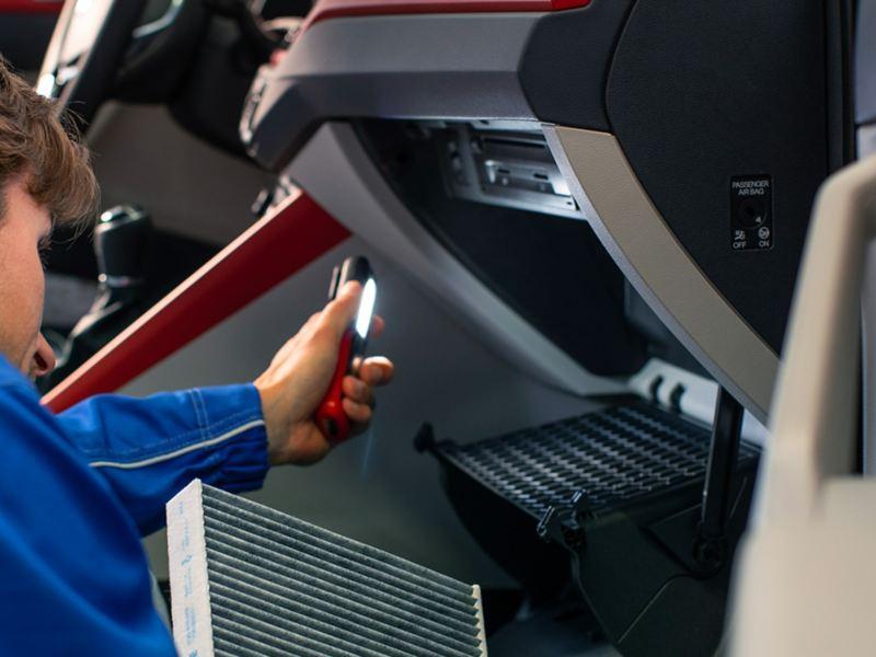 Un addetto di VW Service sta controllando gli interni di una Volkswagen in officina