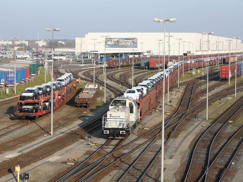 Werkeisenbahn mit Autos auf Waggons