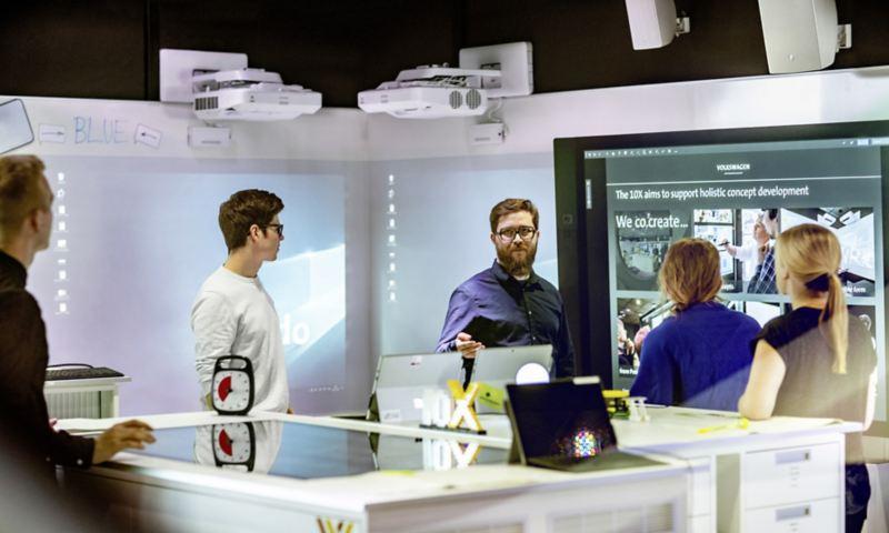 Team arbeitet in der IT-City vor einem großen Bildschirm