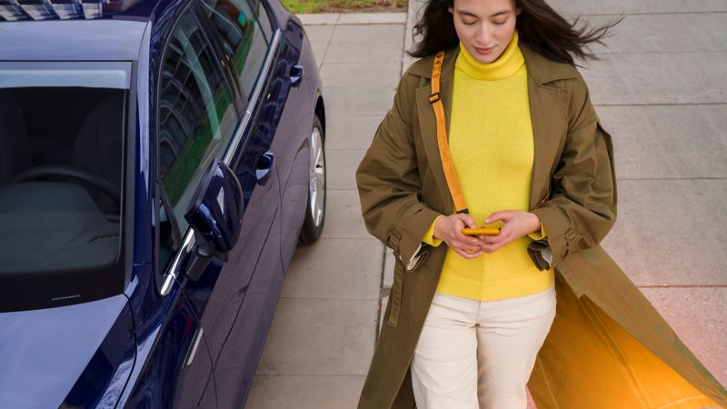 Kvinna med mobiltelefon bredvid bil