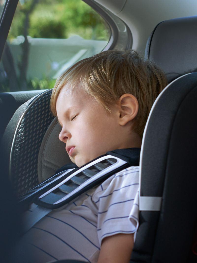 Junge schläft im Kindersitz