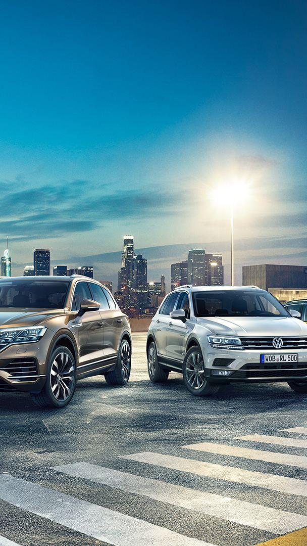 Volkswagenbilar parkerade på kvällen med storstad i bakgrunden