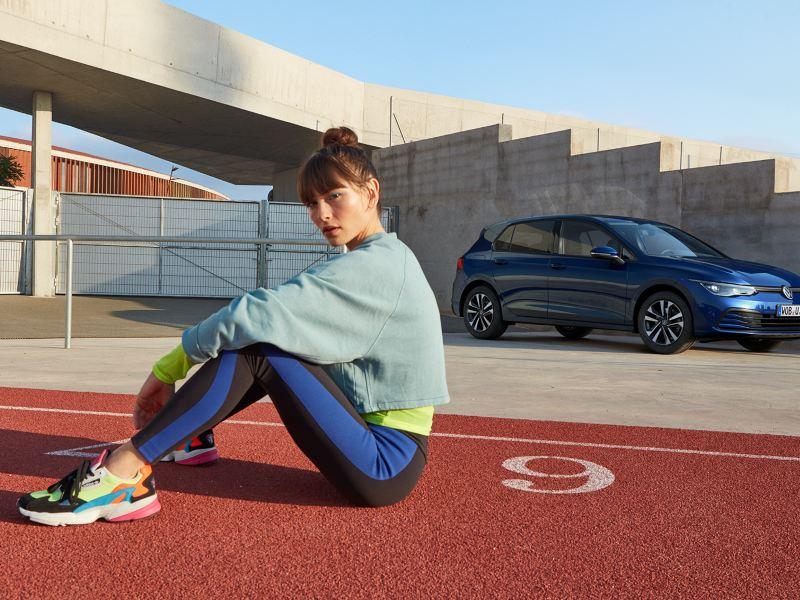 Eine Frau sitzt vor einem VW Golf UNITED in der Seitenansicht.