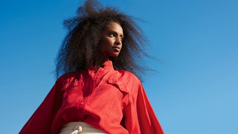 Femme devant un ciel bleu, regardant sur le côté.