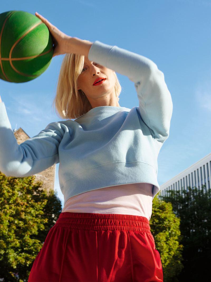 Frau springt mit Basketball in der Hand hoch. Urbanes Setting mit Stadt und Parkanlage im Hintergund. Lifestyle.
