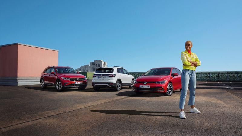 Modèles VW ACTIVE en série spéciale. Gamme avec la Golf ACTIVE rouge, le T-Cross ACTIVE blanc et le Tiguan ACTIVE rouge. Milieu urbain.