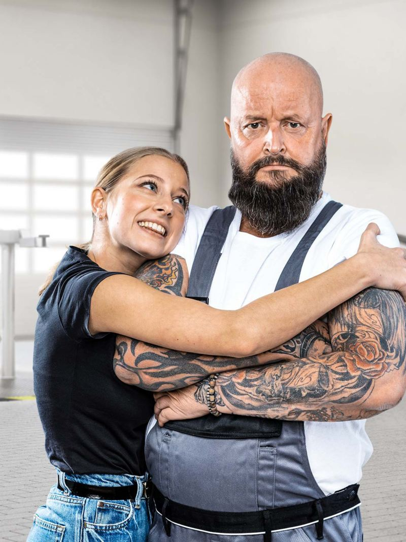 Junge Frau umarmt glücklich einen Werkstattmitarbeiter