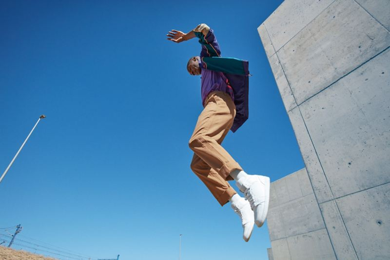 Man jumping in front of concrete facade