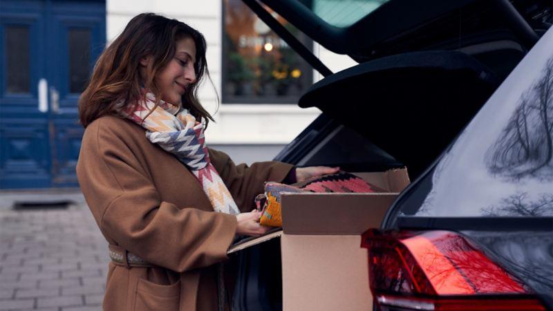 Bote öffnet ein geparktes Auto, um eine We Deliver Lieferung einzustellen.