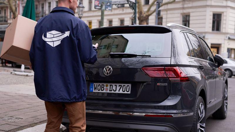 Bote liefert Paket in Kofferraum eines Volkswagen.