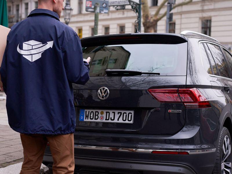 El servicio de mensajería entrega un paquete en un Volkswagen con We Deliver