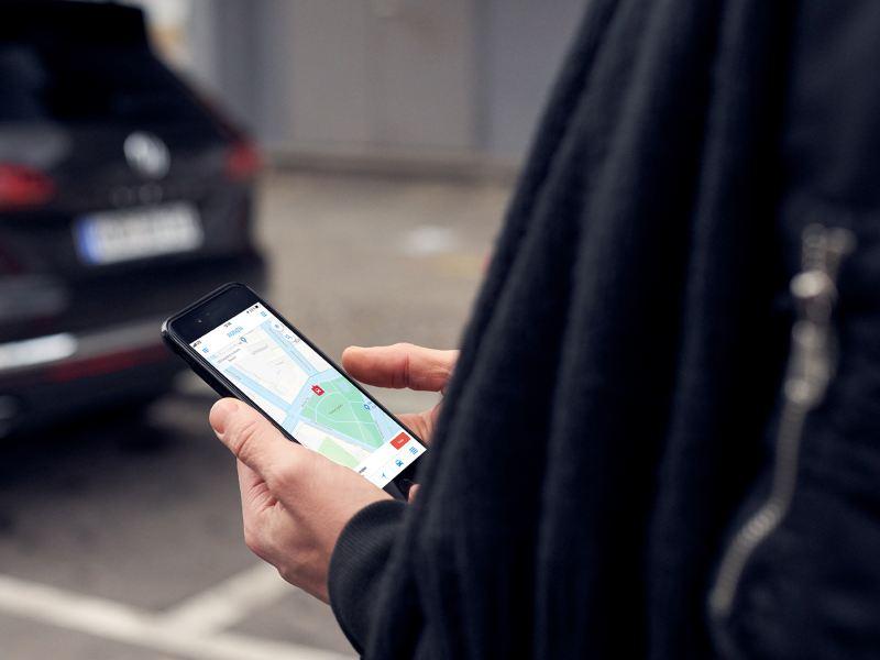 Person guckt auf ein Smartphone mit We Park App.