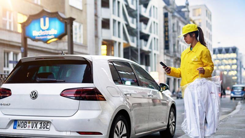 Bote liefert ein Paket in den Kofferraum eines Volkswagen Passat - dank We Deliver.