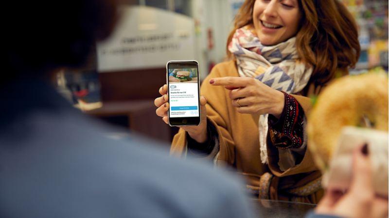 Junge Frau zeigt auf ein Smartphone-Display mit einem Coupon von We Experience.