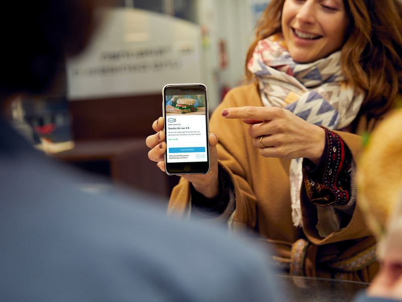 Una mujer joven señala una pantalla de smartphone con un cupón de We Experience.
