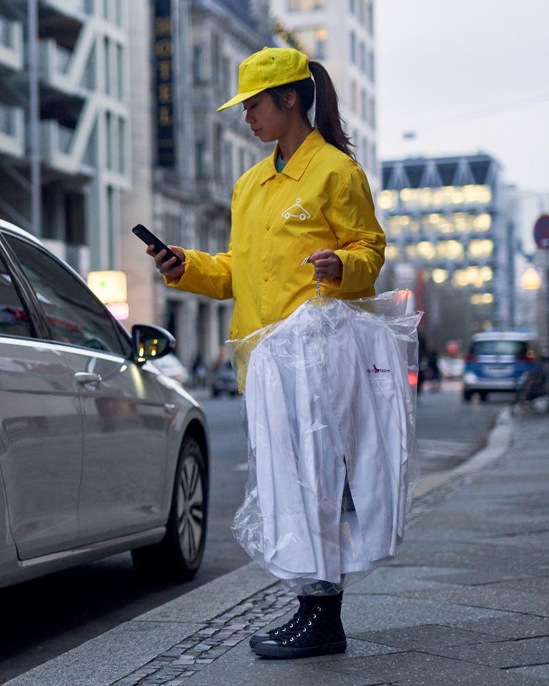 Junge Frau liefert gewaschene Hemden in einen Volkswagen - dank We Deliver.