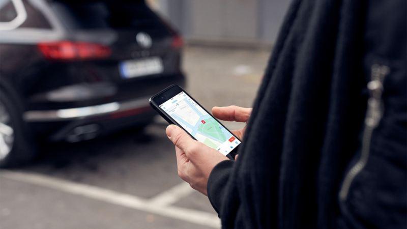 Mann checkt auf Smartphone die We Park App von Volkswagen.