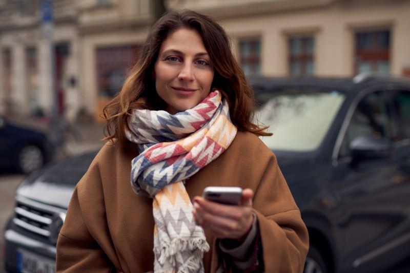 Una mujer con un panecillo en la mano corre hacia su coche.