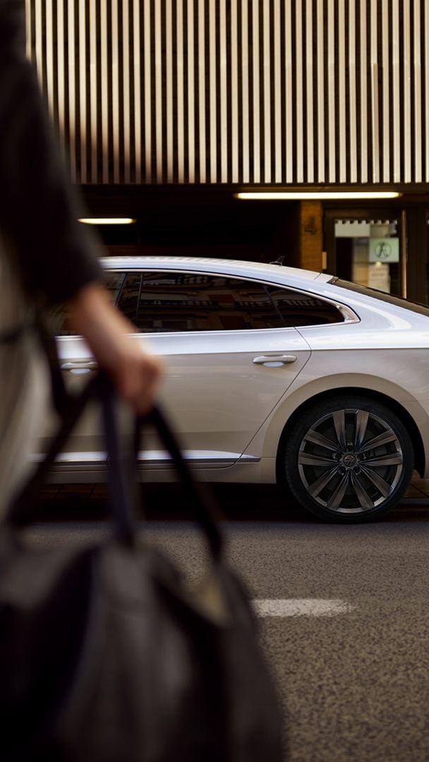 Une femme traversant une route vers Volkswagen Arteon