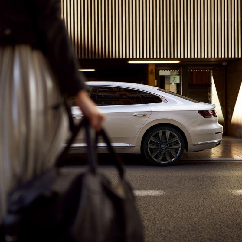 A woman crossing a road towards Volkswagen Arteon