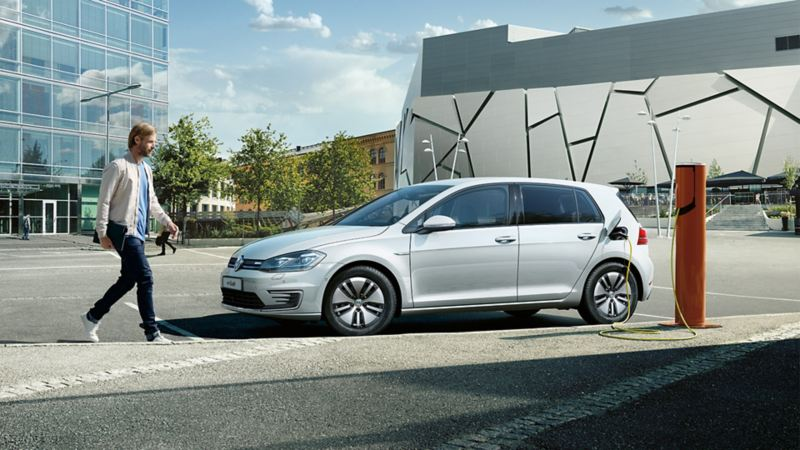 uomo si avvicina a VW e-golf auto elettrica in ricarica
