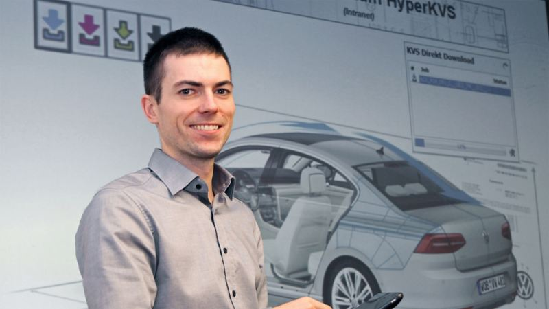 Headshot of a man in front of a vehicle presentation