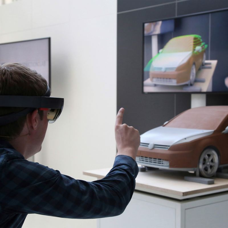 Head of a man wearing VR glasses in front of a vehicle model