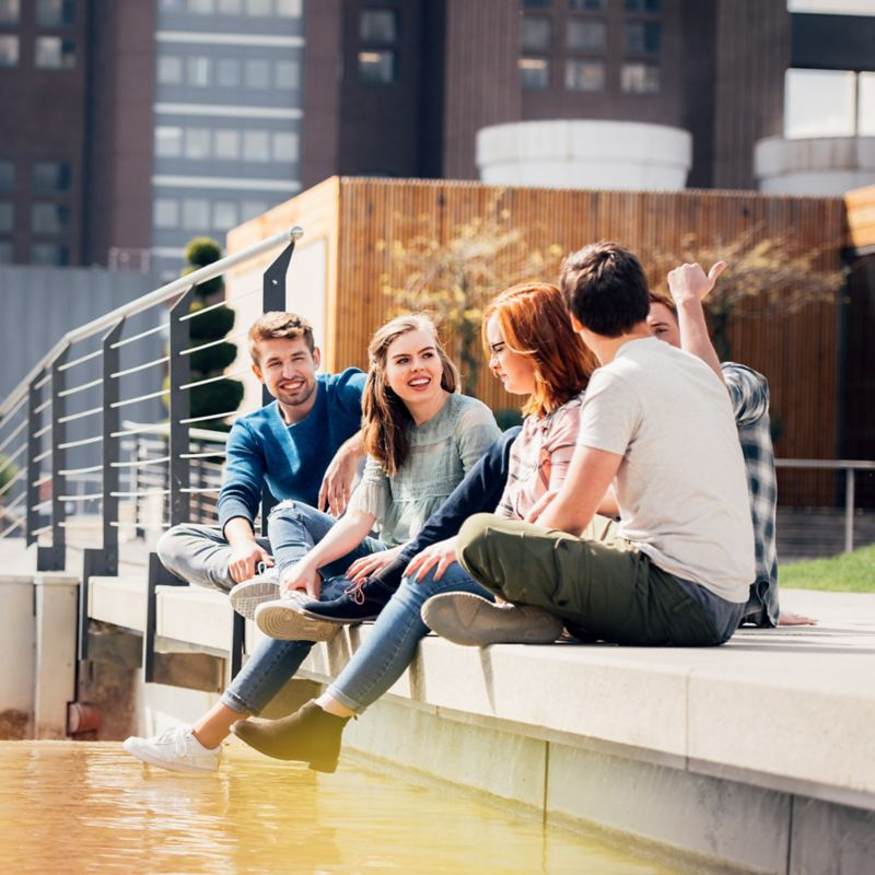 Five young people sitting together at the bank along the water's edge