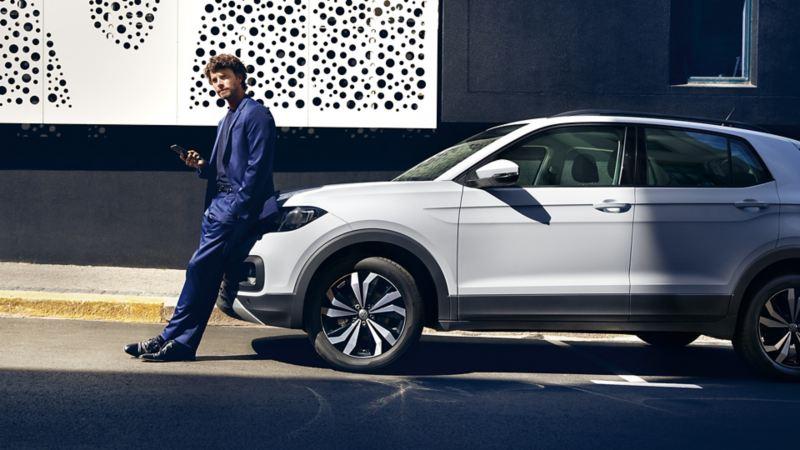 Un uomo appoggiato all'anteriore di una Volkswagen