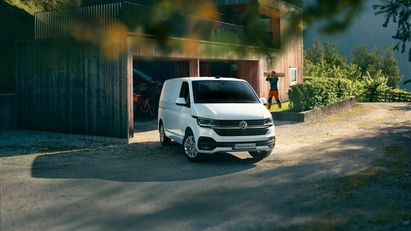 The Transporter 6.1 in front of a wooden house.