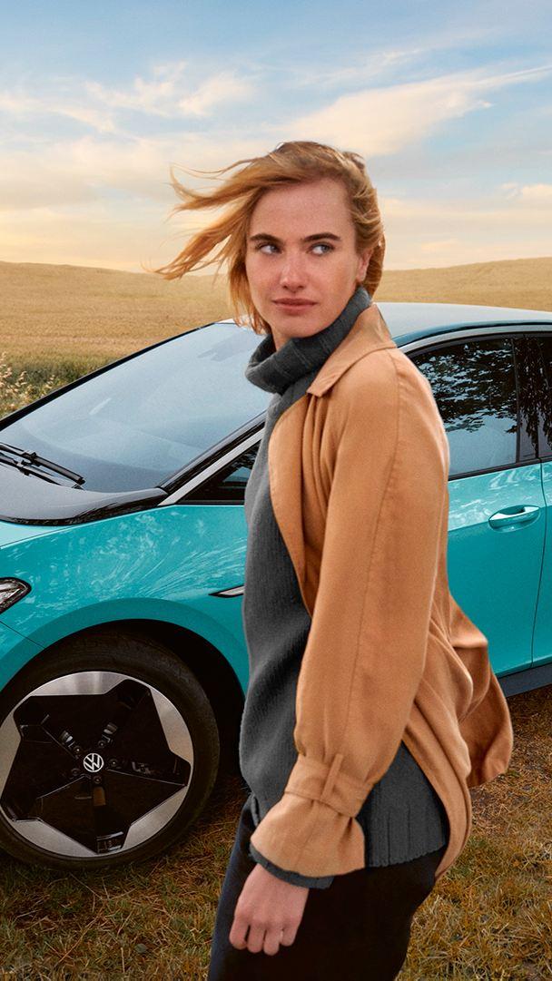 En kvinna står framför en VW ID.3 på ett fält