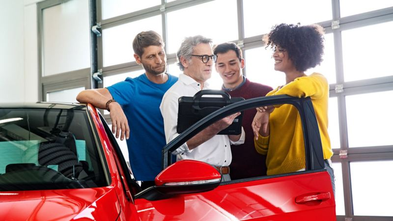 Group of people having a discussion next to a red car