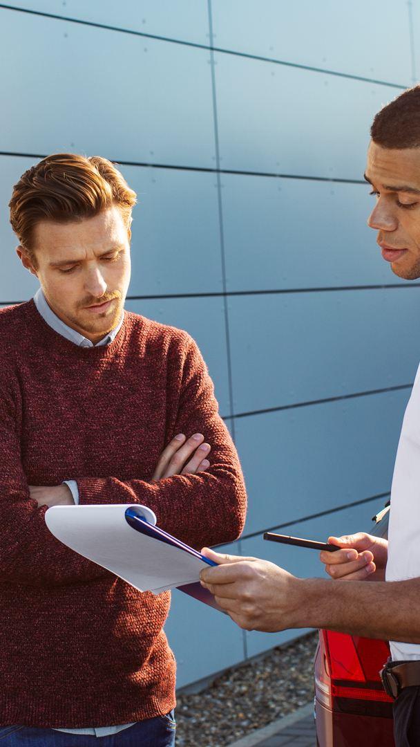 Zwei Männer vor seitlichem Heck, schauen  beide auf ein Schreibbrett mit Unterlagen
