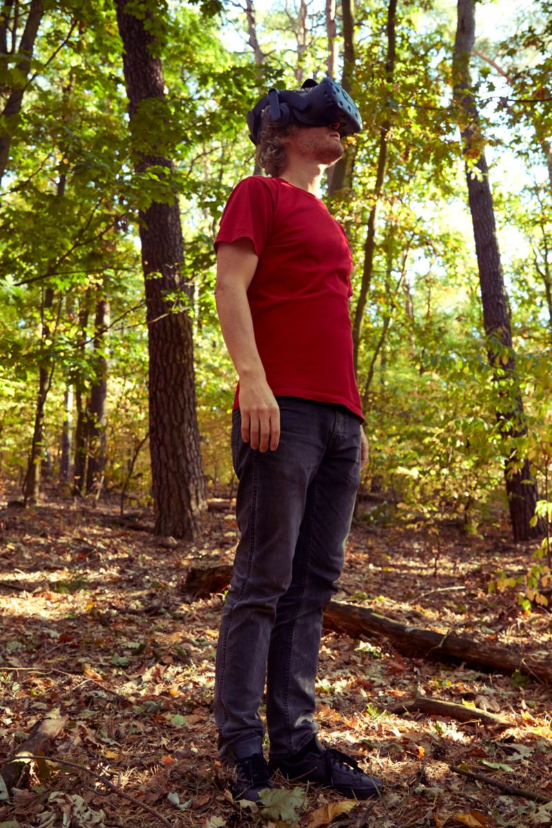 Leo staat met de VR-bril over zijn ogen in de natuur.