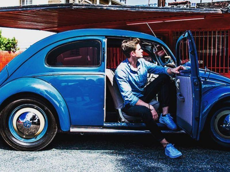 Hombre bajándose de Vocho de Volkswagen en color azul