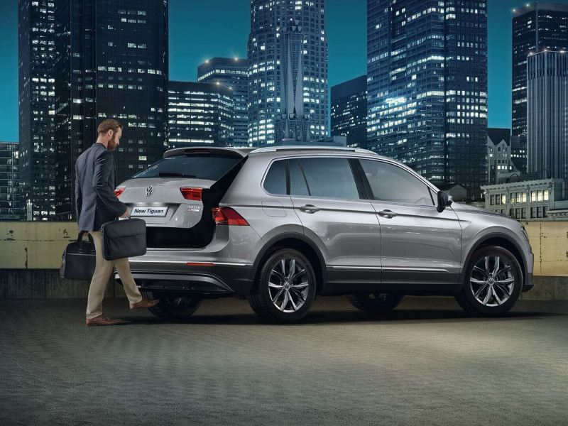 """A Volkswagen Tiguan parked in the city. A man waves his foot under the bumper to open the trunk, using the """"easy open"""" function"""