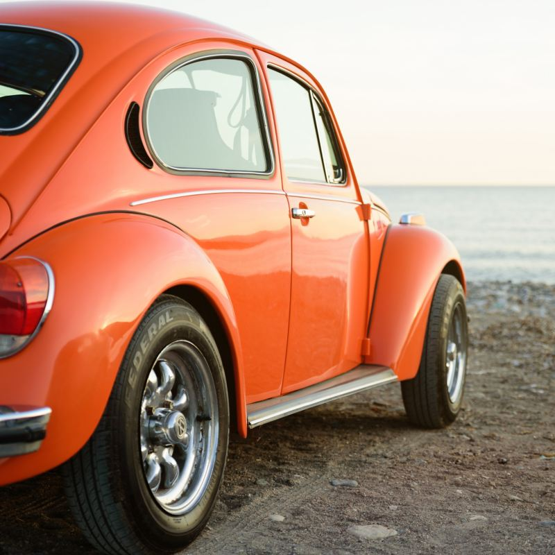 Volkswagen Maggiolino arancione parcheggiato in una spiaggia davanti al mare