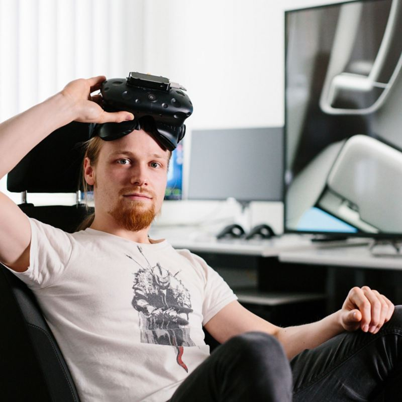A man wearing VR glasses sitting in a driving simulator