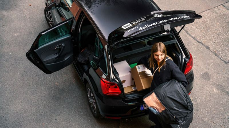 Una mujer joven recoge paquetes del maletero