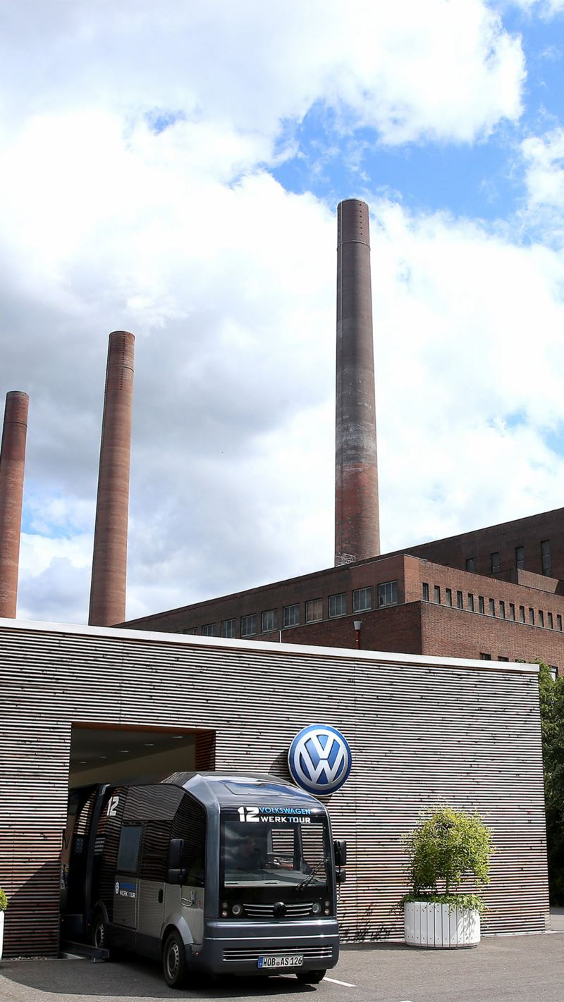 Eine Panormabahn fährt aus einem Gebäude heraus, auf der Wand ist ein Volkswagen Logo