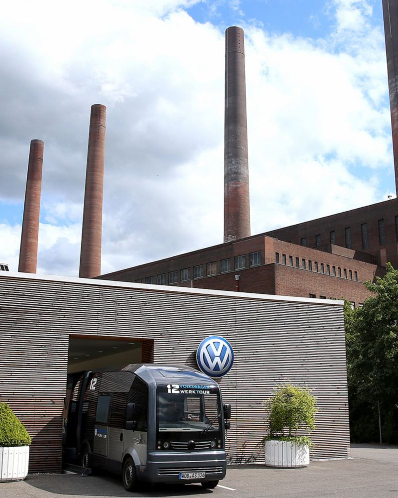 Ein Minibus steht vor dem Volkswagen Werksgebäude mit den vier Schornsteinen